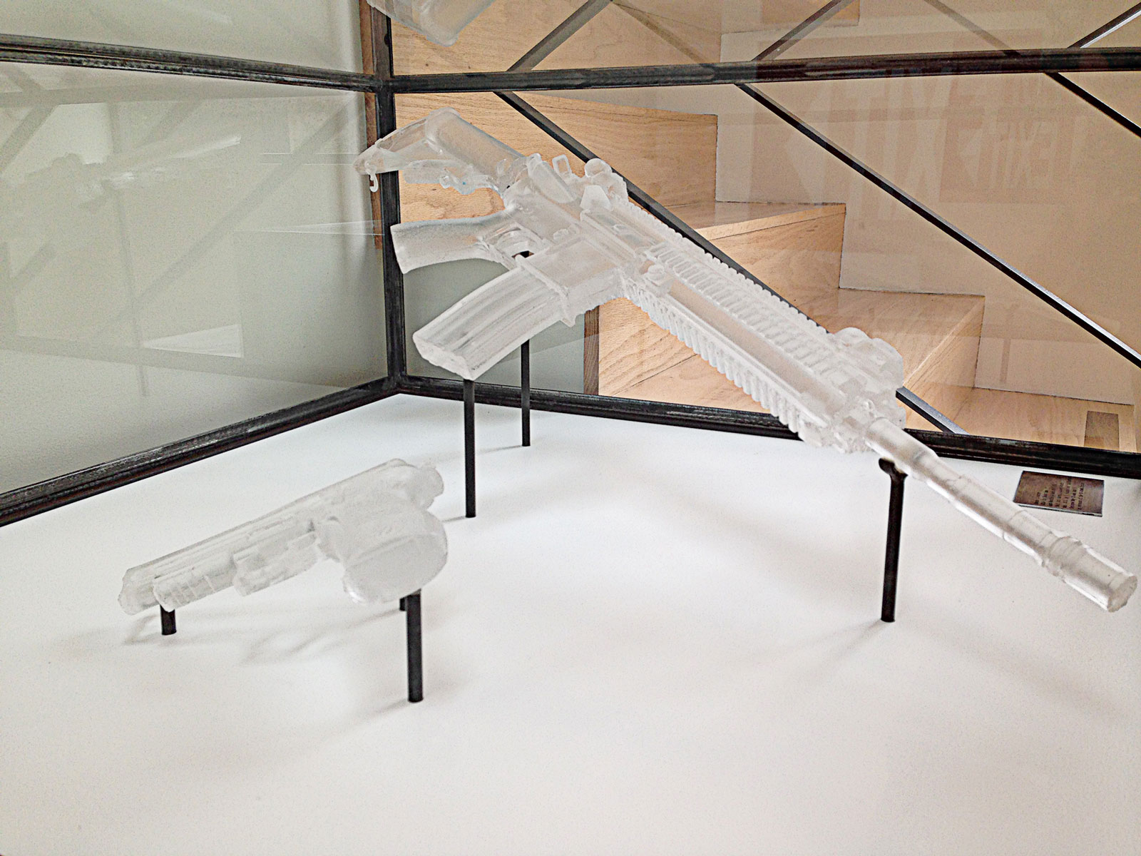 <i>Combat Negatives: P226 Sig Sauer and H&K416</i> (2013). Display case 14˝ × 32˝ × 32˝, sculptural negatives made from cast resin.